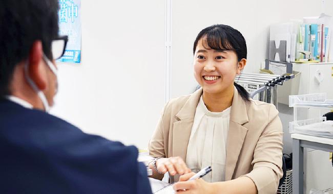 新入社員の女性一人が笑ってはしており、一人の先輩社員の男性の後ろ姿が写っている写真