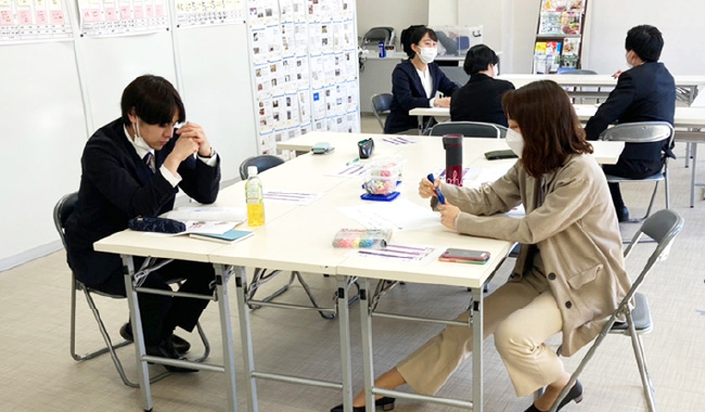 勉強会を開催し、机で黙々と勉強する男性社員と女性社員
