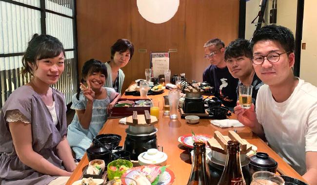 社員が家族と楽しそうに食事をしている写真