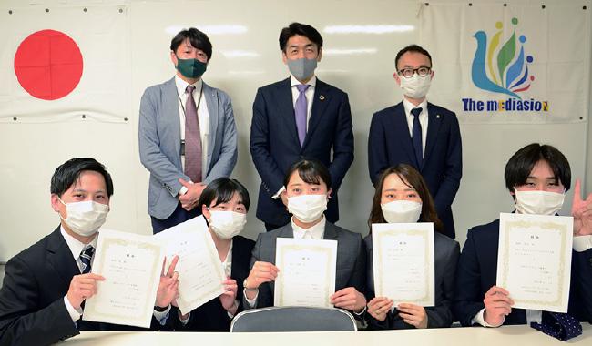 マスクを付けた社員たちが社員総会でいただいた賞状を見せて写っている社員