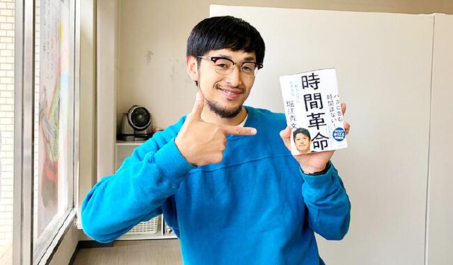 書籍『時間革命』を持って指を刺しながら笑っている社員の写真