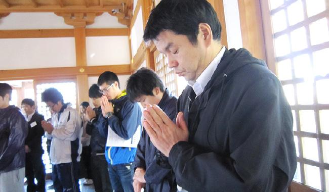 神社に参拝し手を合わせる社員の写真