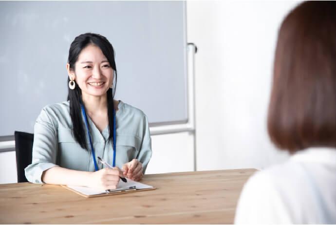 女性社員が学生の話を聞いている写真