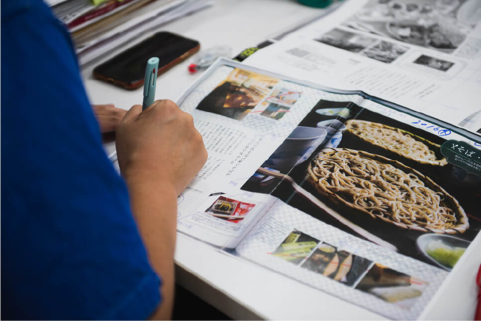 男性が雑誌の校正をしている写真